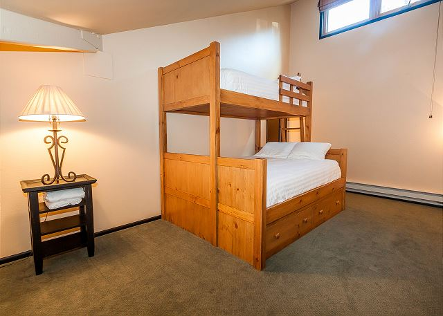 The second bedroom is in the upstairs loft and features a twin over queen bunk bed with Ivory White Bedding. There's also a queen trundle and an en suite bathroom.