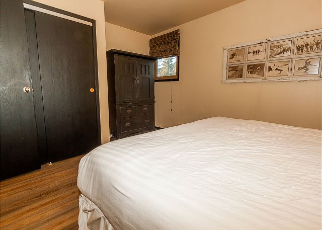 The first bedroom is on the main level and features a king-sized bed with Ivory White Bedding and a flat screen TV.
