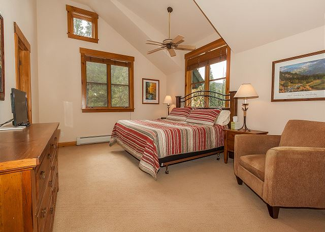 The master bedroom is upstairs and features a king-sized bed and a flat screen TV.