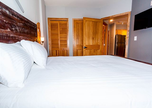 The bedroom features a queen-sized bed with Ivory White Bedding, a mounted flat screen TV and slope views.