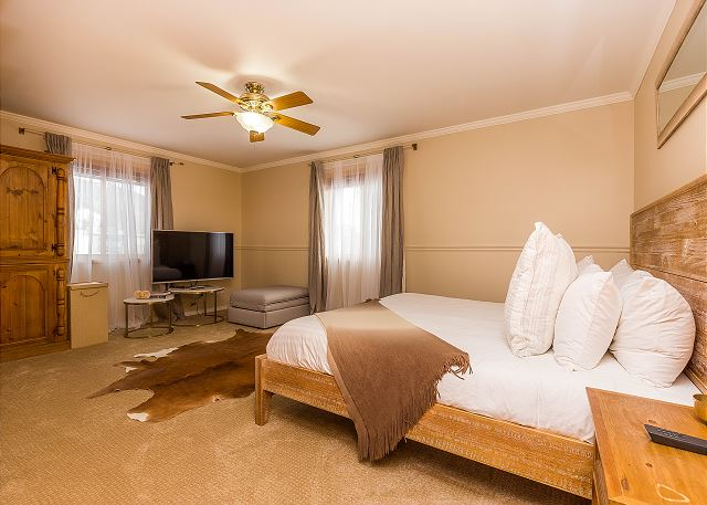 The first master bedroom features a king-sized bed with Ivory White Bedding and a flat screen TV.