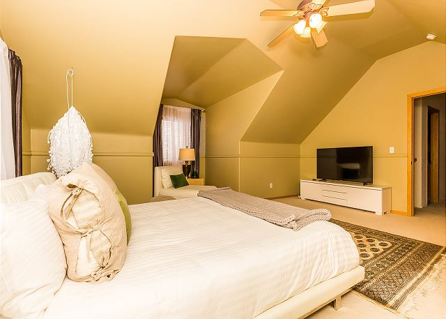 The first guest bedroom is upstairs and features a king-sized bed with Ivory White Bedding and a flat screen TV. There is also a twin-sized sleeper chair.