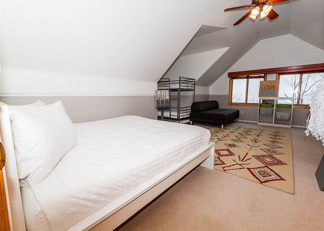 The second guest bedroom is upstairs and features a king-sized bed and a twin-sized bunk bed with Ivory White Bedding. There is also a modern full-sized daybed, a flat screen TV and desk.