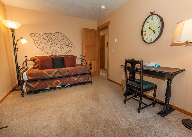 The guest bedroom features a twin-sized bed with a twin trundle. There's also a dedicate workspace with a desk and chair.