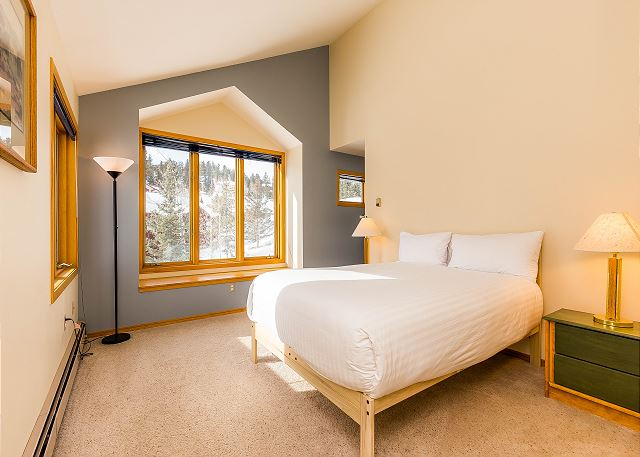 The master bedroom features a queen-sized bed with Ivory White bedding and a bench seat by the window.