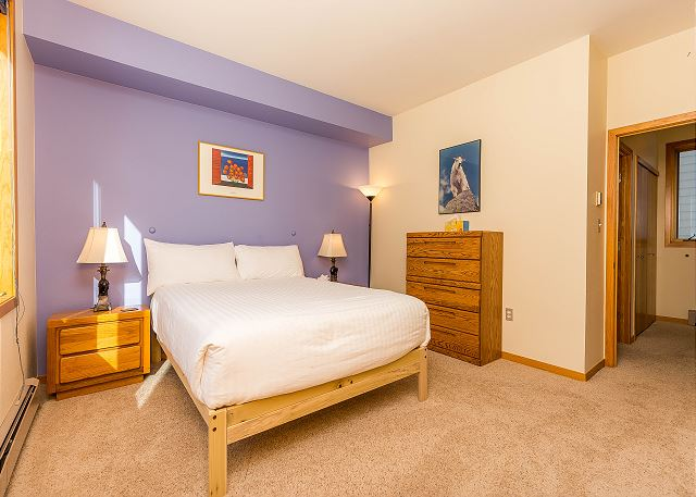 The first guest bedroom features a queen-sized bed with Ivory White Bedding and large windows.