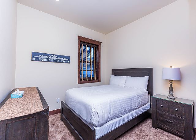 The second guest bedroom is downstairs and features a queen-sized bed with Ivory White Bedding.