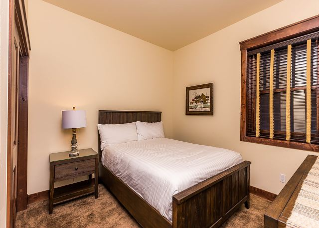 The third guest bedroom is downstairs and features a queen-sized bed with Ivory White Bedding.