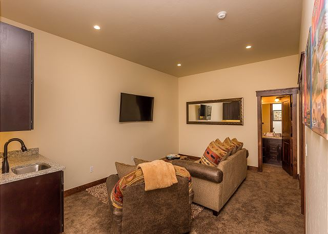 The downstairs den features a mounted flat screen TV, seating and a wet bar.