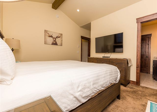 The master bedroom features a king-sized bed with Ivory White Bedding, a mounted flat screen TV and outdoor access.