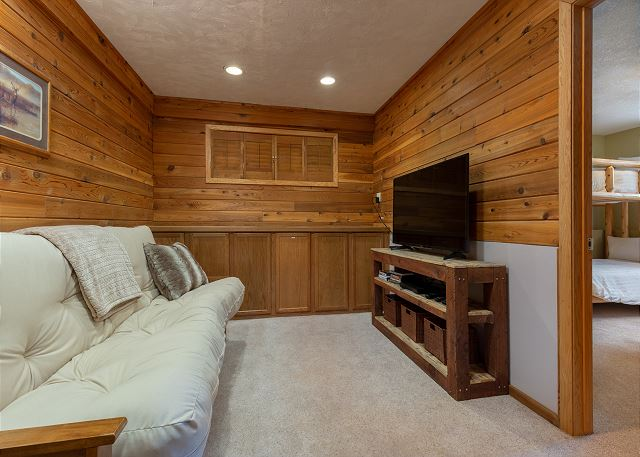 The den in the basement features a flat screen TV and a queen-sized futon.