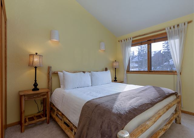 The second master bedroom features a king-sized bed with Ivory White Bedding.