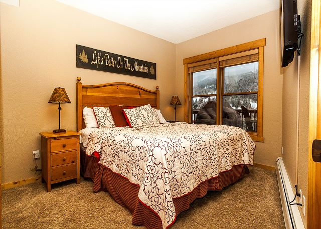 The master bedroom features a king-sized bed, a mounted flat screen TV and beautiful slope views.