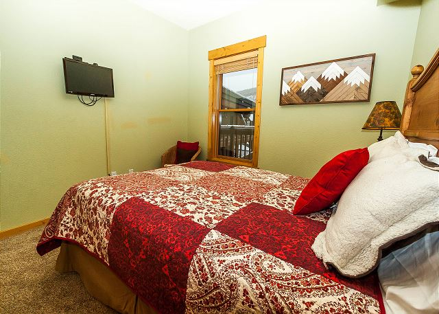 The guest bedroom features a queen-sized bed and a mounted flat screen TV.
