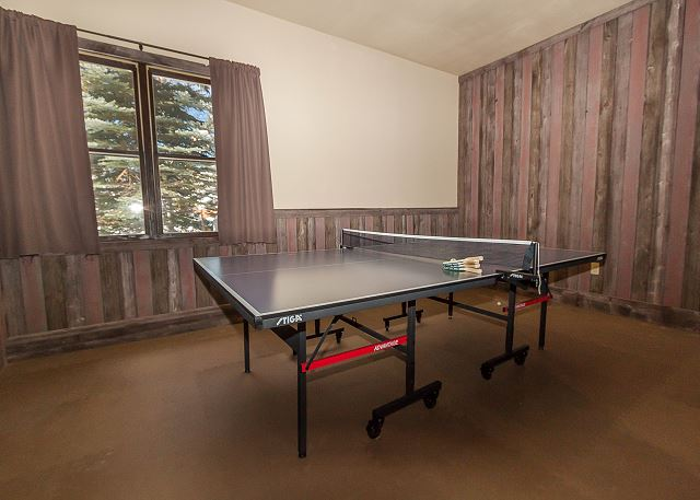 The homeowner has converted the garage into a recreation room with a ping-pong table and a cozy seating around a large flat screen TV.