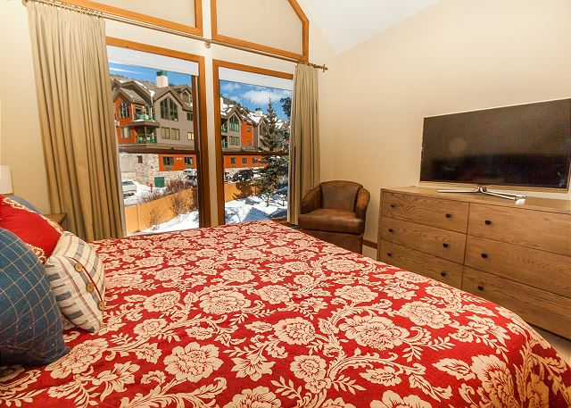 The first master bedroom is on the main level and features a king-sized bed, a flat screen TV and vaulted ceilings.