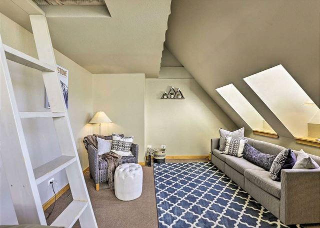 The den offers a cozy seating area with skylights and a small loft with a twin-sized bed.