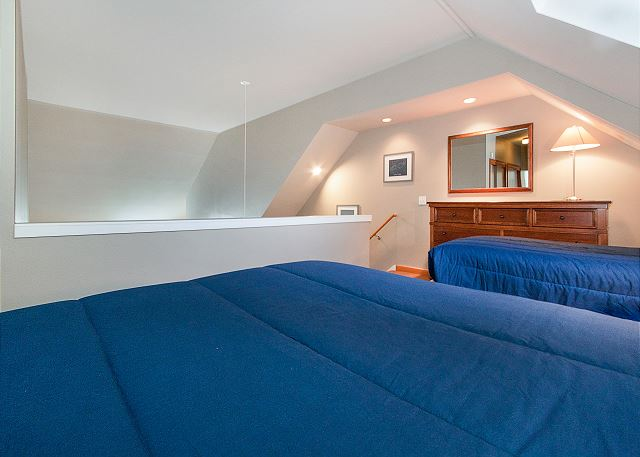 The first guest bedroom is in the upstairs loft and features a twin-sized bed and a full-sized bed.
