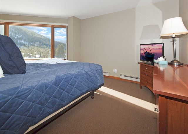 The master bedroom features two twin beds pushed together into a king-sized bed, a flat screen TV and beautiful mountain views.