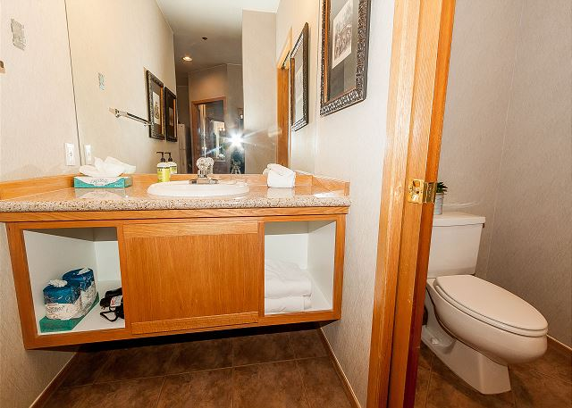 There is a half bathroom across from the bedroom with a single sink vanity and a door separates the toilet area for added privacy.