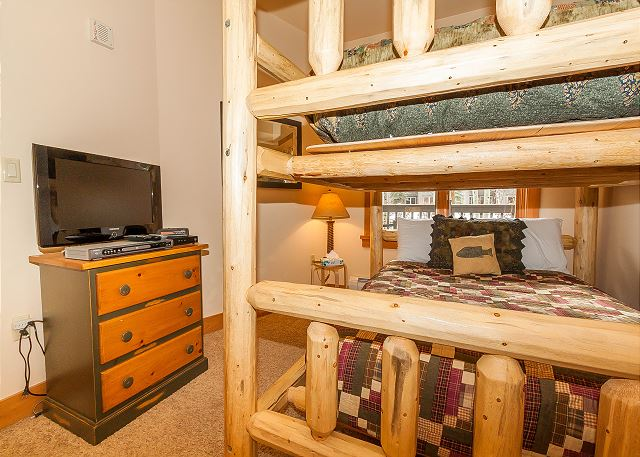 The guest bedroom features a full-sized bunk bed and a flat screen TV.