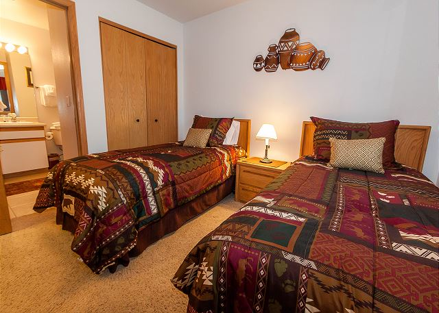 The guest bedroom features two twin-sized beds, a flat screen TV and its own entrance to the guest bathroom.
