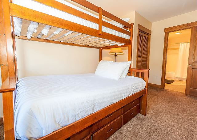 The guest bedroom features a twin-over-full bunk bed on our Ivory White Bedding program, a mounted flat screen TV and its own entrance to the guest bathroom.