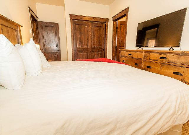 The second master bedroom features a king-sized bed with Ivory White Bedding and a Smart TV.