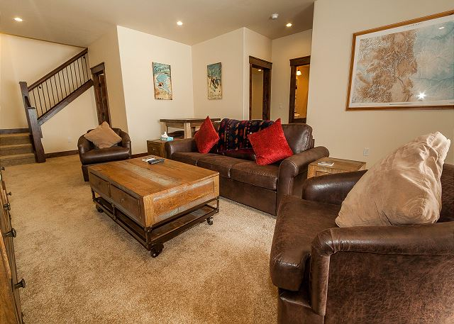 The family room is downstairs and has a large flat screen TV and queen-sized sleeper sofa. There's also a game table and a walk-out patio.