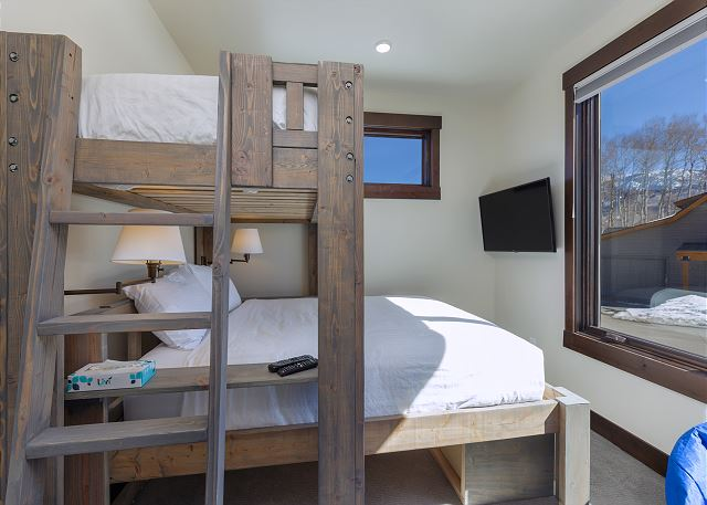 The second guest bedroom features a twin-over-queen bunk bed with Ivory White Bedding and a mounted flat screen TV.
