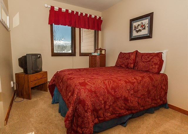 The second guest bedroom features a full-sized bed and a television.