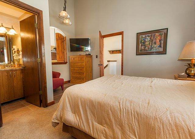 The master bedroom is upstairs and features a queen-sized bed and a flat screen TV.
