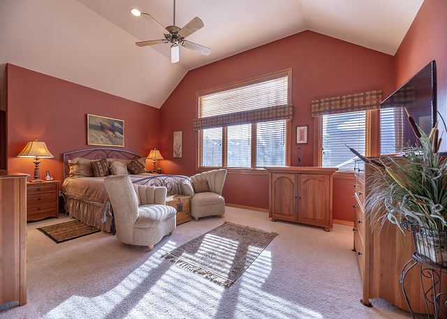 The first master bedroom is upstairs and features a king-sized bed, a flat screen TV and comfortable seating area.