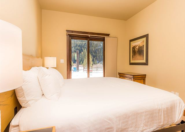 The first guest bedroom is downstairs and features a king-sized bed with Ivory White Bedding and its own private patio.