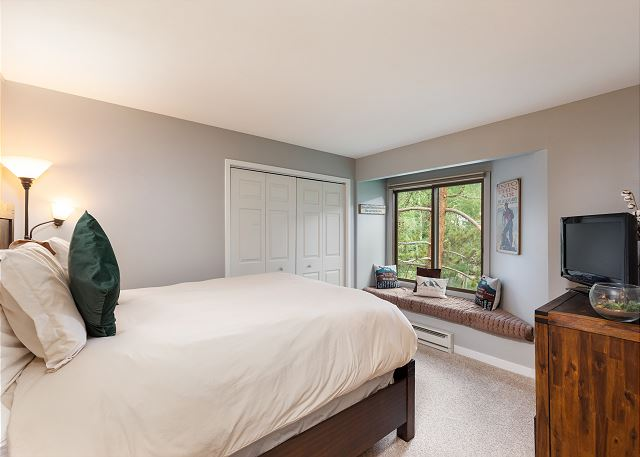 The master bedroom features a queen-sized bed, a window seat and a flat screen TV.