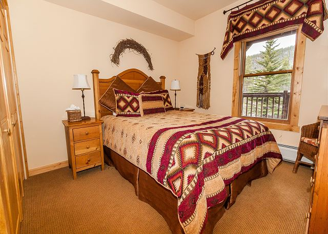 The guest bedroom features a queen-sized bed and a flat screen TV.