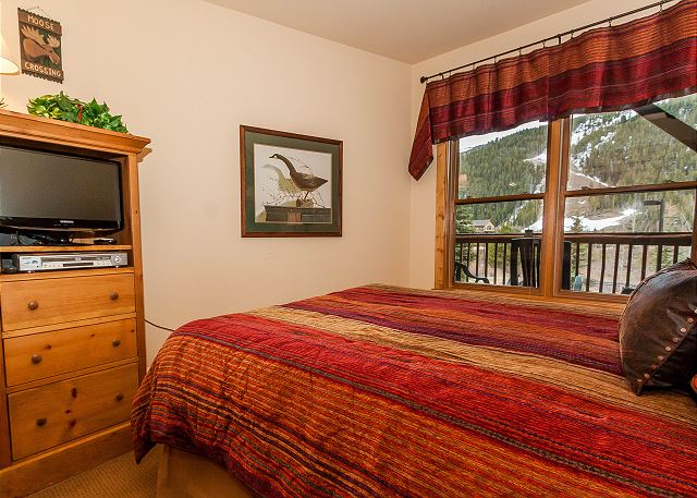 The master bedroom features a queen-sized bed, a flat screen TV and beautiful slope views.