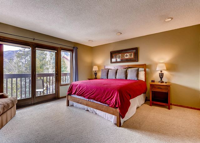 The master bedroom features a king-sized bed, a mounted flat screen TV and its own private balcony.