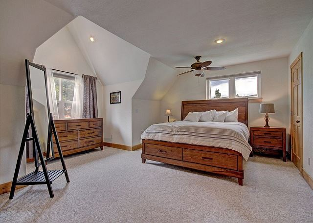 The master bedroom is upstairs and features a king-sized bed, a flat screen TV and an en suite bathroom.