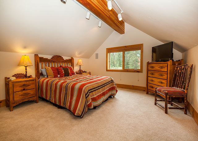 The second master bedroom is upstairs and features a queen-sized bed and a flat screen TV.