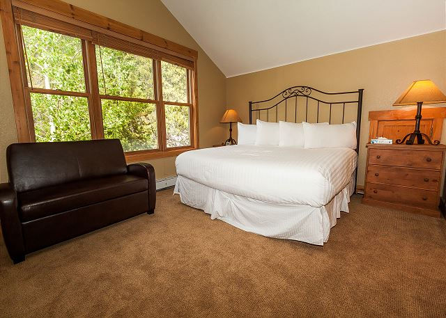The first master bedroom is upstairs and features a king-sized bed with Ivory White Bedding, a twin-sized sleeper chair and a flat screen TV.