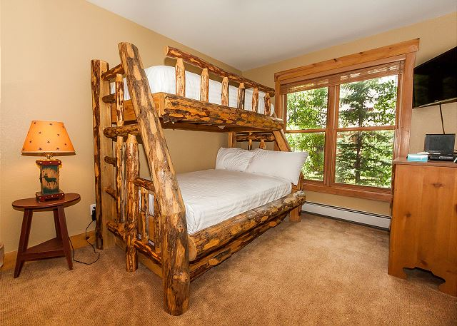 The first guest bedroom is on the main level and features a twin-over-full bunk bed with Ivory White Bedding and a twin trundle. There is also a mounted flat screen TV.