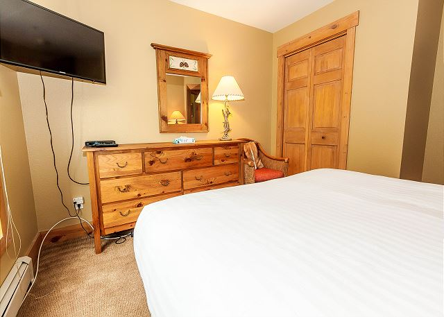 The second guest bedroom is on the main level and features a queen-sized bed with Ivory White Bedding and mounted flat screen TV.