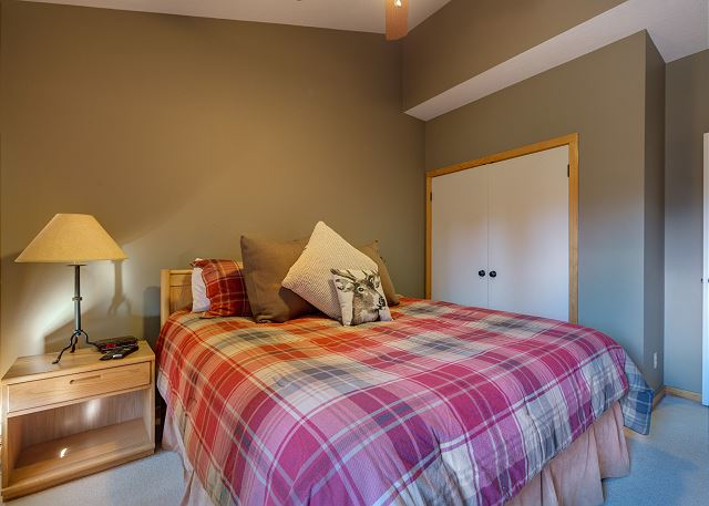 The first guest bedroom features a king-sized bed and a mounted flat screen TV.