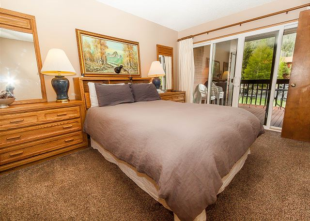 The master bedroom features a queen-sized bed, a mounted flat screen TV and access to the private balcony.