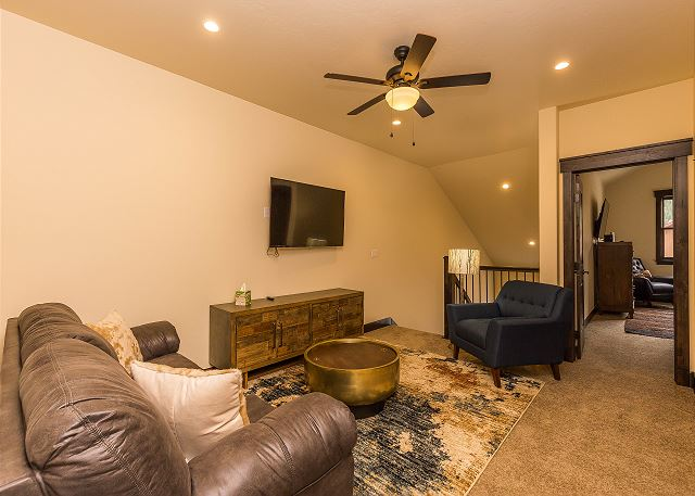 The loft on the third level features a mounted flat screen TV and a queen-sized sleeper sofa.