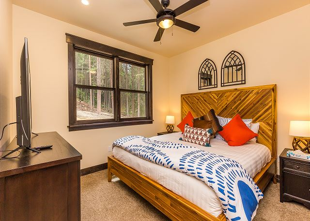 The first guest bedroom is on the second level and features a king-sized bed with Ivory White Bedding and a flat screen TV.