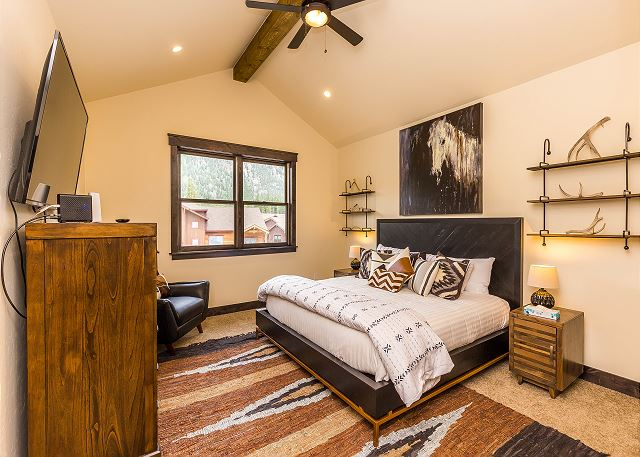 The master bedroom is on the third level and features a king-sized bed with Ivory White Bedding and a mounted flat screen TV.