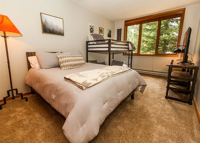 The guest bedroom features a queen-sized bed, a twin-sized bunk bed and a flat screen TV.