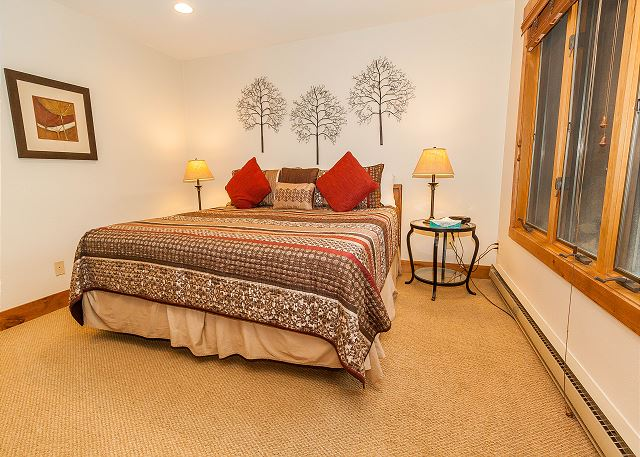 The first master bedroom features a king-sized bed and a flat screen TV.